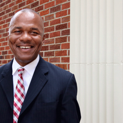 Tyrone Jackson poses outside in suit and tie with a brick wall background