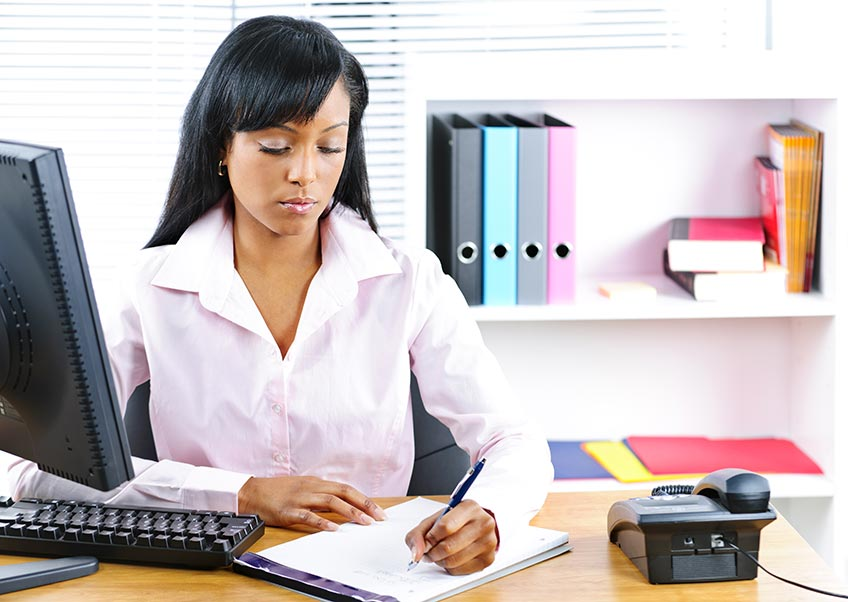 woman with notepad and pen woking at her desk