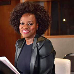 Viola Davis sitting in broadcasting room smiling with microphone above