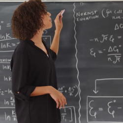 woman writing on a chalkboard while she's teaching class
