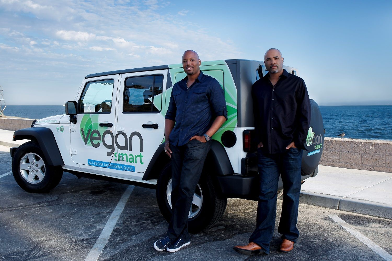 Kareem Cook and Claude Tellis stand in front of the promotional truck parked in a parking lot