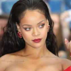 Rihanna poses in red dress and red lipstick