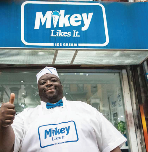 Mikey owner of Ice Cream shop stands outside in his uniform holding a thumbs up