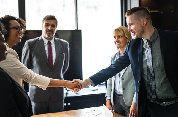 woman shaking mans hand in a room withdiverse co-workers