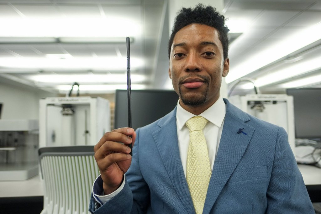 Lamonte Pierce dressed in a suit holding his straw invention