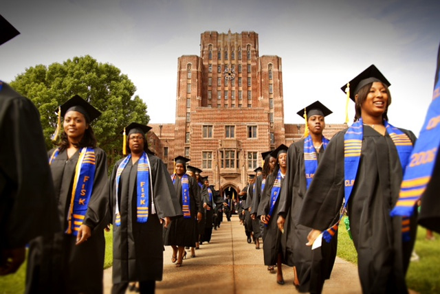 graduates walking in cap and gowns on HBCU campus