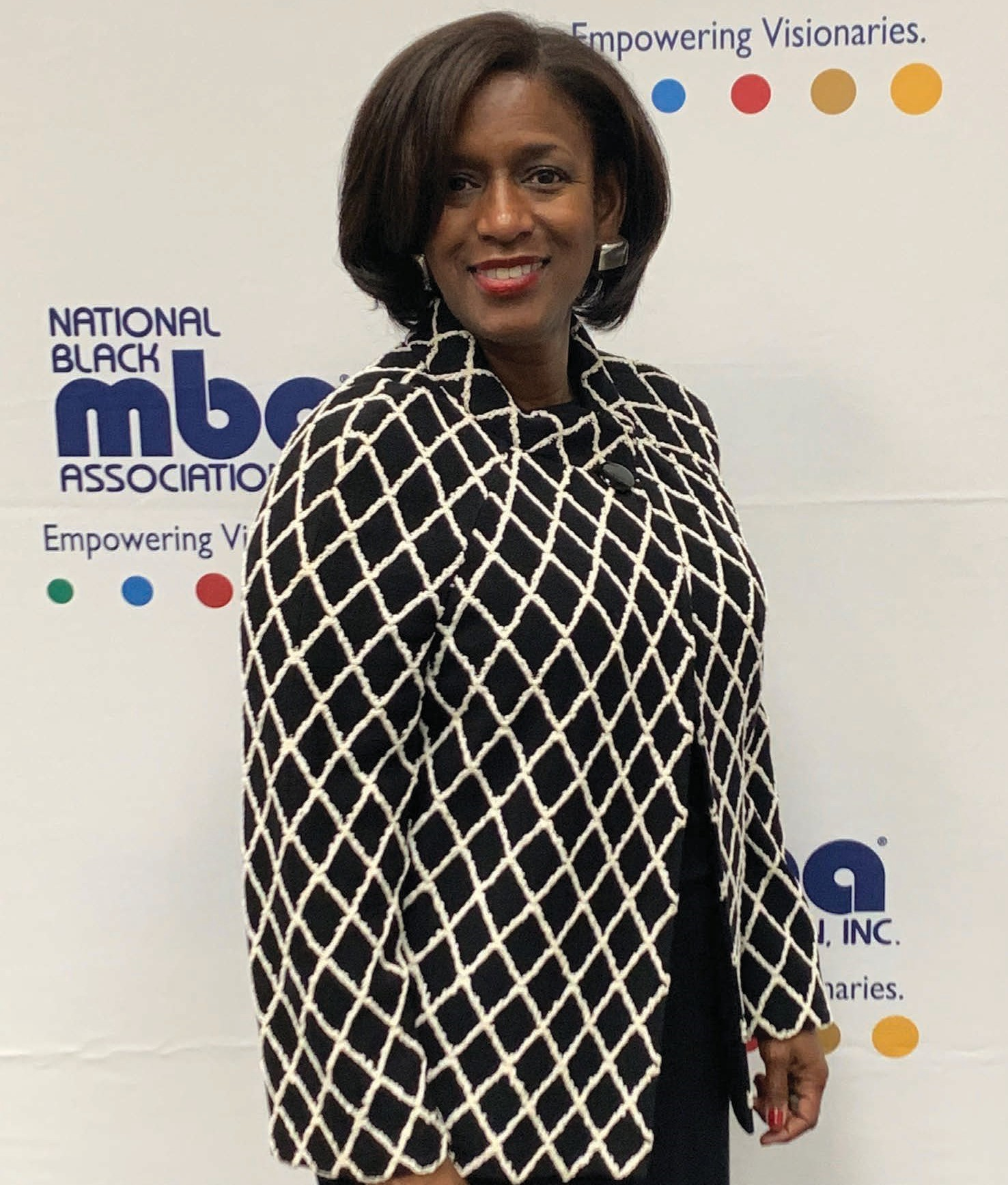 Kay Wallace of the National Black MBA Association stands with a dress suit on in front of a NBMBAA logo filled canvas for picture taking