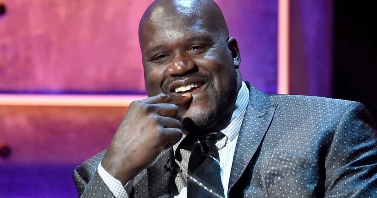 Shaquille O'Neal smiling wearing a suit