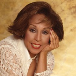 Diahann Carroll pioneering actress poses in a white dress with gold background