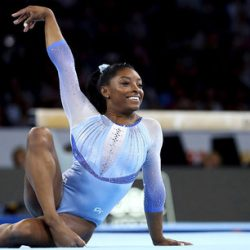 Simone Biles posing on gymnatict floormat after performance smiling with hand in the air