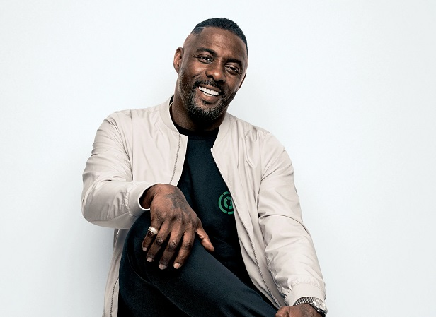 Idris Elba sittting casually, smiling with one hand on his knee