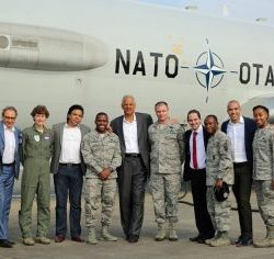 Stedman Graham pictured in front of large military plane with several servicemembers