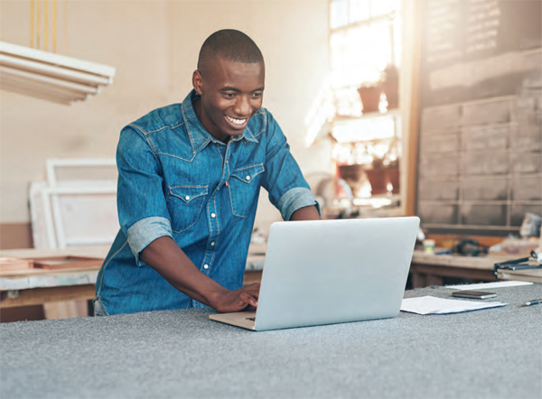 black man looking excitedly at his laptop
