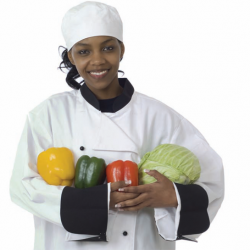 Female chef wearing her uniform holding fresh vegetables