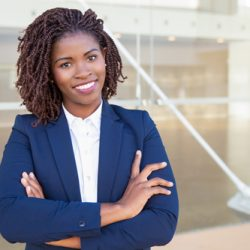 Happy successful professional posing near office building. Young African American business woman with arms folded standing outside, looking at camera, smiling