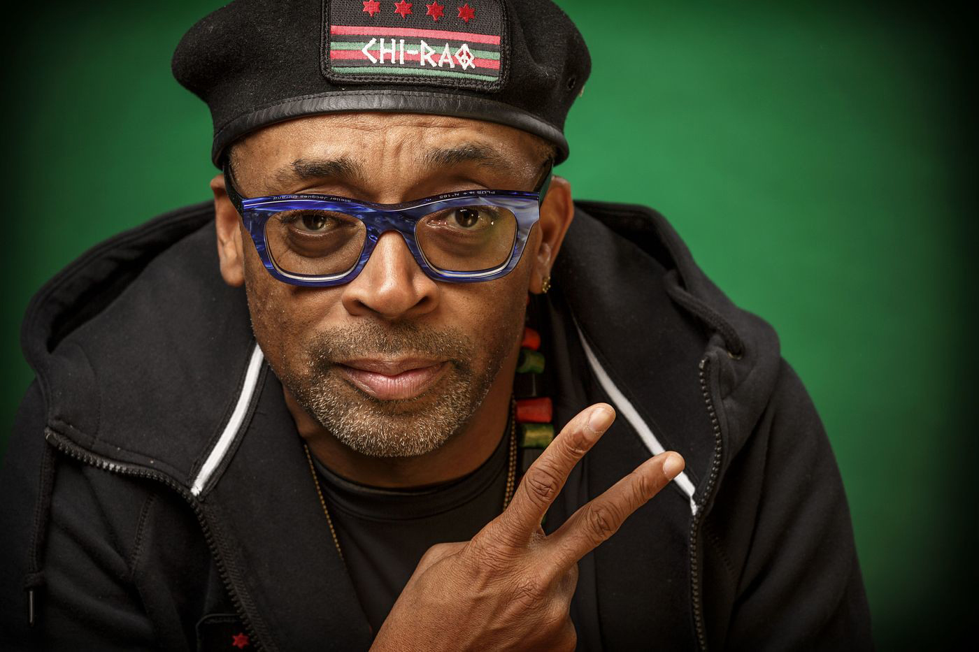 Spike Lee pictured in cap and giving the peace sign