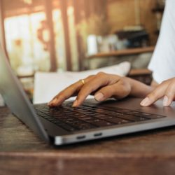 Closeup of woman's hand iworking by touching laptop