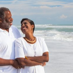 African American man and woman couple looking at each other on a deserted tropical beach