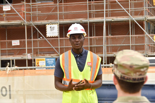 Oluwaferanmi Ogundana, a Morgan State University junior civil engineering major, is interviewed at a construction site, Camp Humphreys, South Korea, July 15. Ogundana is currently working as an intern at the U.S. Army Corps of Engineers, Far East District, as a part of the Advancing Minorities wearing a hard hat inside a warehouse.