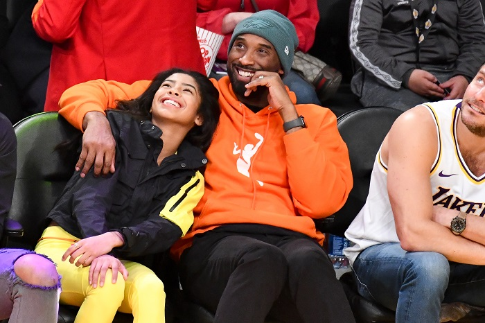 Kobe and Gigi seated at basketball game and Kobe's arm is placed lovingly around daughter