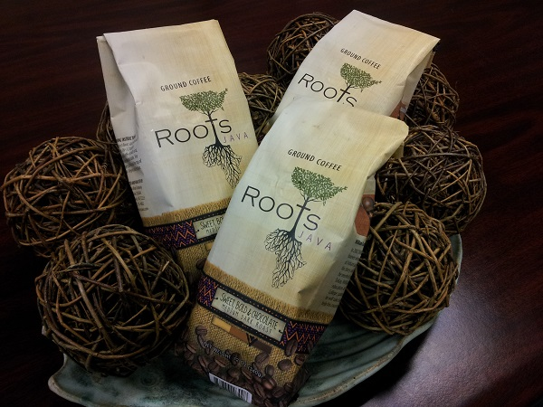 Three bags of Root Coffee sitting in a bowl with balls made of twine