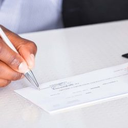 man writing paycheck from company
